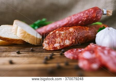 Italian Ham And Salami With Herbs, Garlic And Baguette Slices. High Quality Photo.