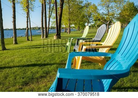 Colorful Adirondack Chairs On The Green Grass Near The Shoreline Of A Beautiful Minnesota Lake On A