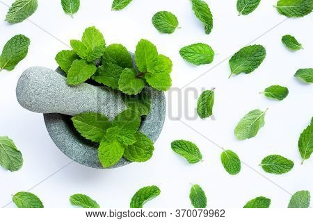 Mint Leaves In Stone Mortar And Pestle On White Background. Top View