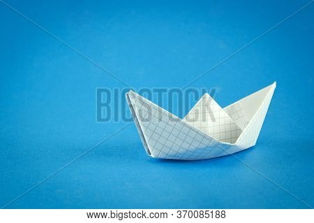 Paper Boat On A Blue Background, A Boat Floating On The Water, A Symbol Of Hope, Origami, Classic Bl
