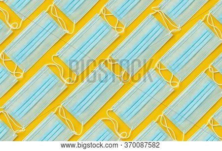 Layout of disposable medical face masks on yellow background. Personal protective equipment, PPE.