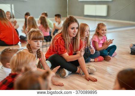 Full Length Portrait Of A Postive Young Dance Teacher Talking To Group Of Little Happy Girls And Boy