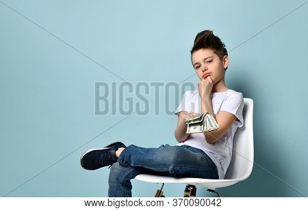 Boy Sits On Chair Holding Dollars And Touching Chin With Hand Thinking How To Earn More. Big Salary,