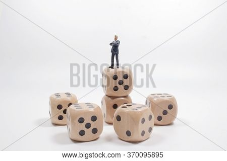 Business Figure Dice. Standing On Mountain Of Colored Dice.