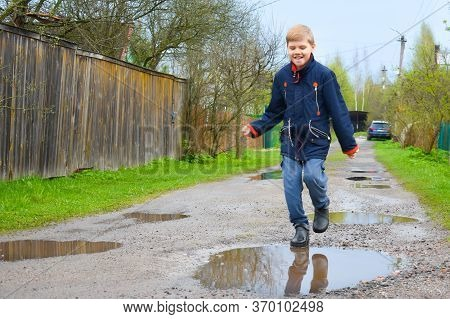 Boy Jumping In A Mud Puddle. The Child Stepped In A Water Puddle On The Road. A Happy Childhood In T