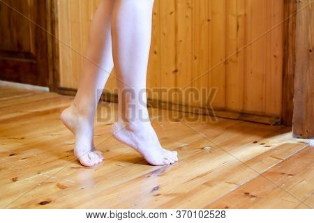 A Woman Is Tiptoeing Barefoot On A Wooden Floor In A Room. Sneaking Slowly On Tiptoe.