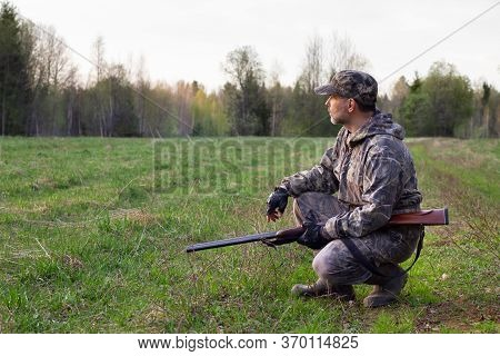 A Hunter With A Shotgun In His Hands Squats And Looks At A Forest Clearing In The Evening In The Spr