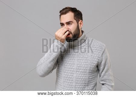 Young Bearded Man In Gray Sweater Posing Isolated On Grey Wall Background, Studio Portrait. Healthy