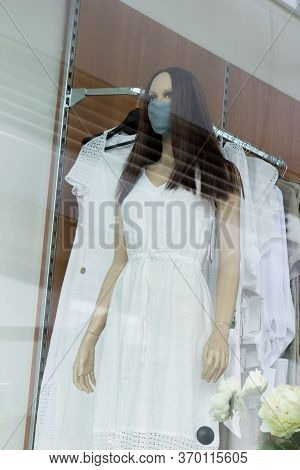 Mannequin In A White Summer Long Dress, With A Medical Protective Mask On His Face, Long Hair And A
