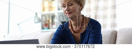 Elderly Woman Uses A Bank Card To Pay Online. Woman In Casual Clothes Sitting At Home On Sofa In Fro