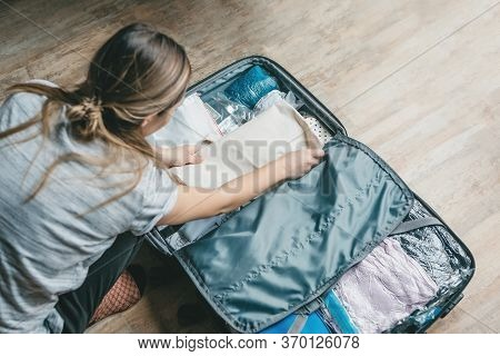 A Girl Is Packing Clothes Or Unpacking Things From A Suitcase. Preparing For A Travel During The Hol