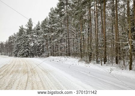 Winter Paved Road With Ruts From Cars In Winter, Covered With Snow After Snowfall, On The Surface Of
