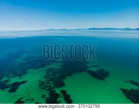 Aerial View. Coast Of Gimsoya Island. Clear Turquoise Sea Water Surface With Mountains On Horizon. N