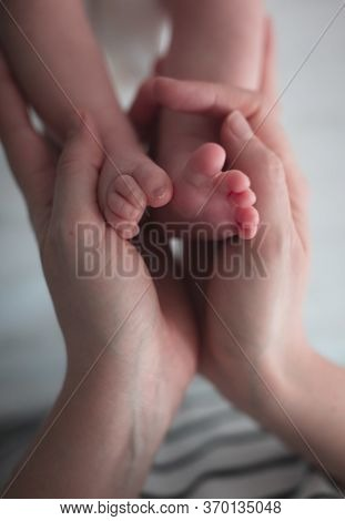 Woman Hands Holding Baby Feet Closeup With Copy Space
