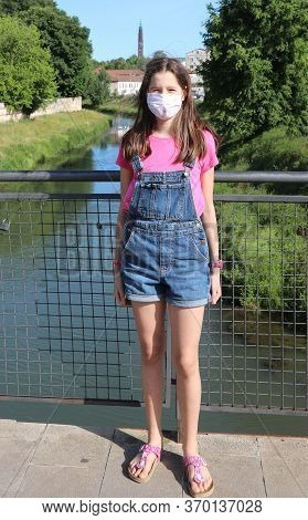 Little With With Jeans And Surgical Mask And River In Background