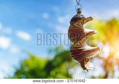 Old Wooden Wind Chimes Hanging Over Blue Sky