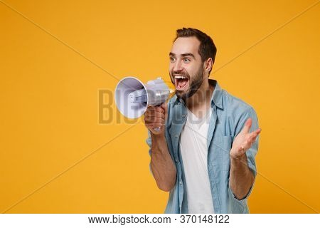 Excited Young Man In Casual Blue Shirt Posing Isolated On Yellow Orange Background Studio Portrait.
