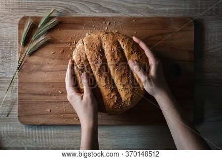 Woman Hands Holding A Home Made And Baked Grain Bread On A Wooden Table With Floral Decoration And C