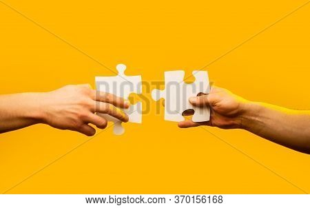 Two Hands Trying To Connect Couple Puzzle Piece On Yellow Background. Teamwork Concept. Holding Puzz