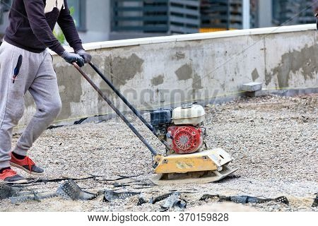 A Road Worker Uses A Gasoline Stove To Compact Crushed Stone At The Site Of Road Repair And Subseque