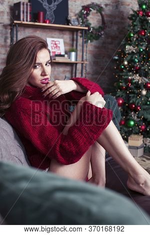 Young Pretty Stylish Woman In Red Winter Sweater At Couch In Home Interior Happy Smiling, Lifestyle