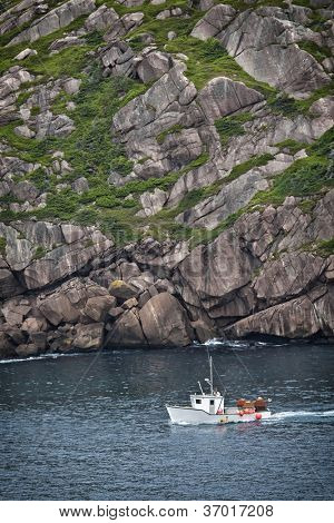 Fishing boat laded with crab traps sailing into St. John's Harbour past Signal Hill, Newfoundland.