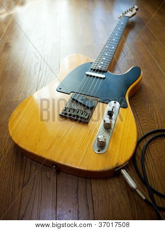 Vintage solid body guitar,plugged in and on the floor.