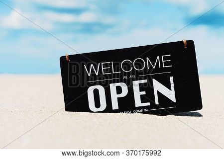 Open Sign On Tropical Sand Beach With Blue Sky Background. Summer Vacation And Travel Holiday Concep