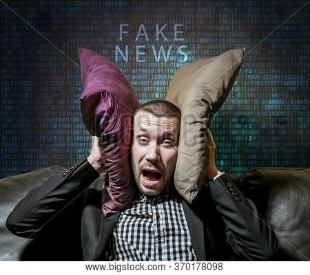 The Man Covered His Ears With Pillows From Fake News Against The Background Of Matrix Numbers