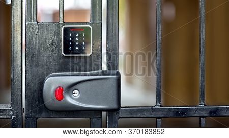 A Security Lock On Black Iron Gate With A Touch Panel For Access Code Key Or A Classic Key In The Ke