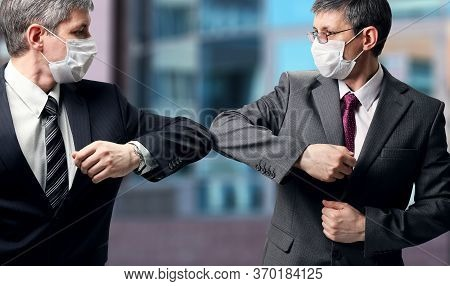 Two Businessmen With A Medical Mask On Their Faces Greet In A New Way, Striking With Their Elbows In