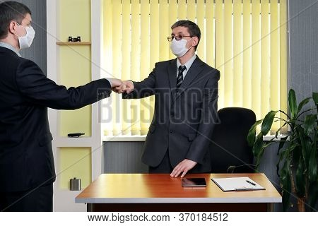 Man In A Suit And Medical Face Mask Got Up From The Table To Greeting Fist Bump On Who Came To His O