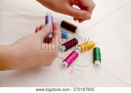 Female Hands Hold Skeins Of Thread On A Beige Background. Silk Threads For Embroidery. Skeins Of Yel