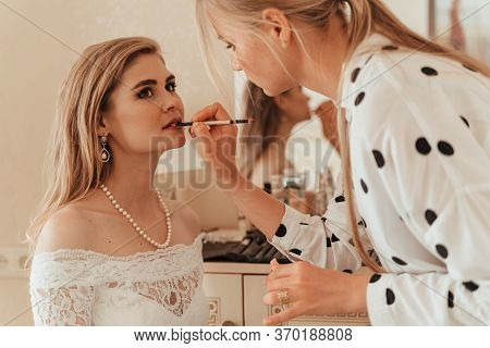 Make-up Artist Makes Professional Makeup For A Young Woman, A Bride. The Bride In A White Dress, A P