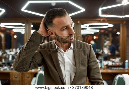 Perfection. Handsome Bearded Man At Barbershop. Portrait Of Stylish Young Guy In Jacket Touching His
