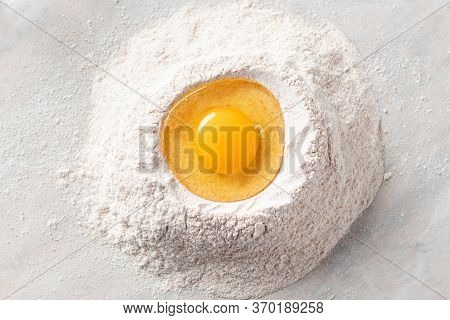 Fresh Egg In A Heap Of Whole Grain Flour On A Marble Table. Basic Baking Ingredients. Top View. Hori