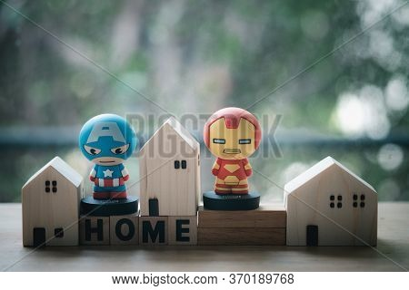 Bangkok, Thailand - June 7, 2020: Superhero With Miniature Wood Home. Concept Of Hero At Home. Conce