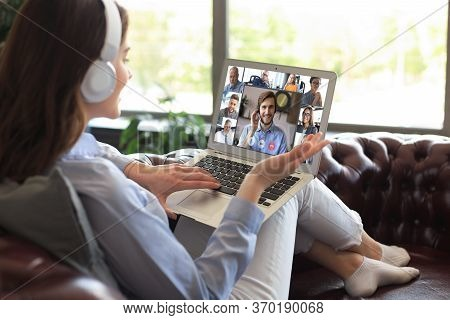 Business Woman In Headphones Lying On Sofa Speak Talk On Video Call With Colleagues On Online Briefi