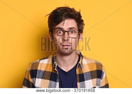 Shocked Puzzled Caucasian Man In Eyeglasses With Wild Hair Opened Mouth Posing On Yellow Studio Wall