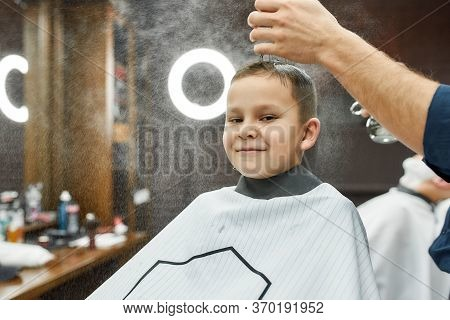 Portrait Of Smiling Cute Boy Sitting In Armchair And Looking At Camera, While Male Barber Preparing
