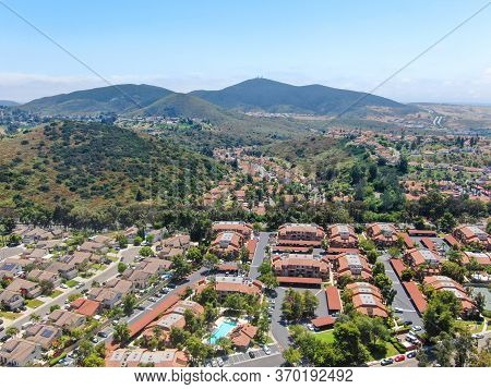 Aerial View Middle Class Neighborhood With Condo Community And Residential House And Mountain On The