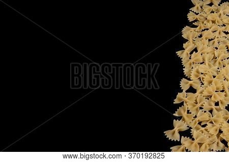 Farfalle Raw Pasta On Black Background. Cooking Concept. Top View With Copy Space.
