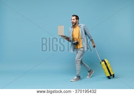 Excited Traveler Tourist Man In Yellow Clothes With Photo Camera Suitcase Isolated On Blue Backgroun