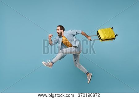 Side View Of Funny Traveler Tourist Man In Yellow Clothes Isolated On Blue Background. Male Passenge