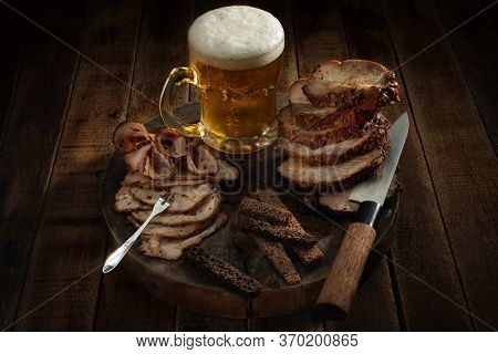 Slices of pastrami pork grilled with spices and honey with glass of beer and rye crackers on a wooden board with knife and  delicatessen fork.