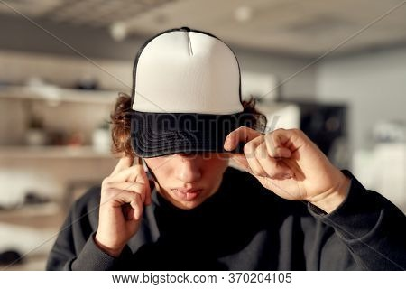 Stylish Guy Looking Down While Posing In Custom Apparel, Black Baseball Cap And Sweatshirt. Young Ma