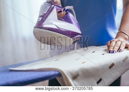 The Girl Holds An Iron On An Ironing Board With A Ferry And Irons Things. Cleaning Service Of The Ap
