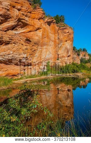 Huge slopes of red sandstone. Small puddle reflects rocks and sky. Paria Canyon-Vermilion Cliffs Wilderness Area. Arizona, Utah. USA. The concept of active, extreme and photo tourism