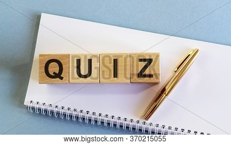 Text Word Inscription Quiz On Cube Blocks With Golden Pen On White Planner Notebook On Blue Backgrou