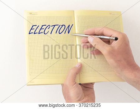 Election Word Written On A Yellow Notebook Or Planner. Male Hand With A Pen Pointing At Planner Page